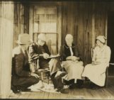 4 people on the porch of old home