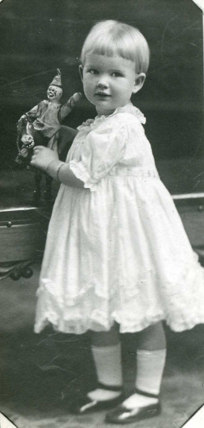 two year old little girl holding clown toy in white dress, mary jane style shoes
